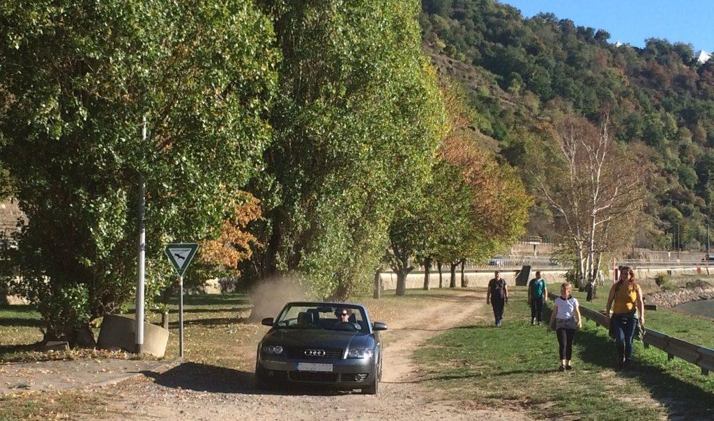 Cabrio mit Staubwolke im Landschaftsschutzgebiet, dahinter Wanderer